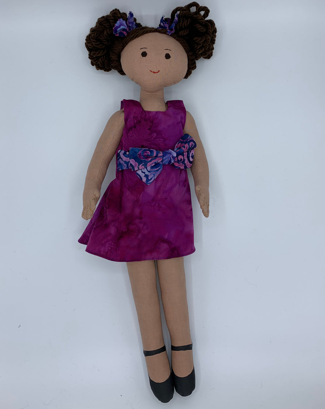 18 inch cloth doll with light brown skin wearing a purple dress