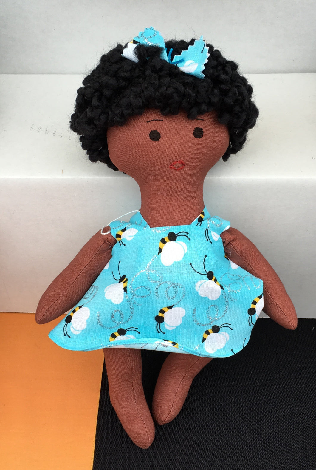 medium brown African-American baby doll with afro and light blue dress