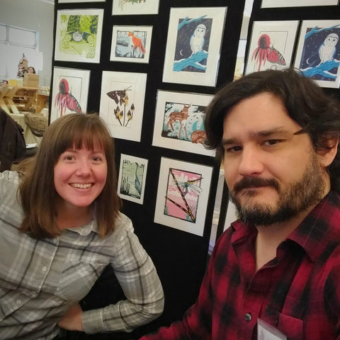 David and Jennie in front of a display of screen print artwork.