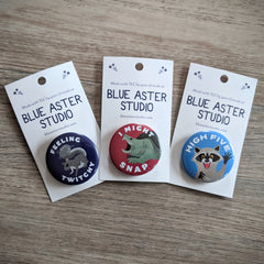 "A collection of wildlife themed buttons. The first has an illustration of a squirrel with the words ""Feeling Twitchy."" The second is an illustration of a snapping turtle with the words ""I Might Snap."" And the third is an illustration of a raccoon with its hand up and the words ""High Five."""