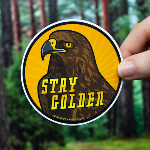 "A round sticker with the text ""stay golden"" and an illustration of a golden eagle."