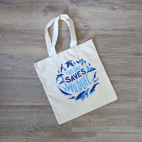 "An organic cotton tote bag with the words ""This Bag Saves Wildlife"" and illustrations of ocean wildlife screen printed on it in two shades of blue"
