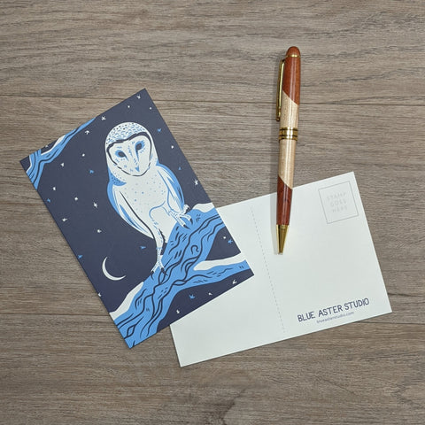 A postcard featuring an illustration of a barn owl sitting next to a pen.