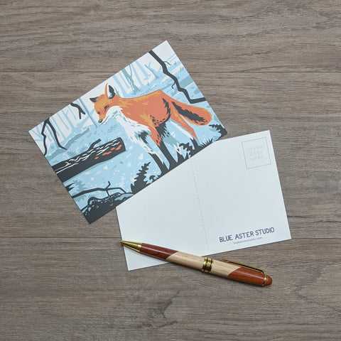 A postcard featuring an illustration of a red fox sitting next to a pen.