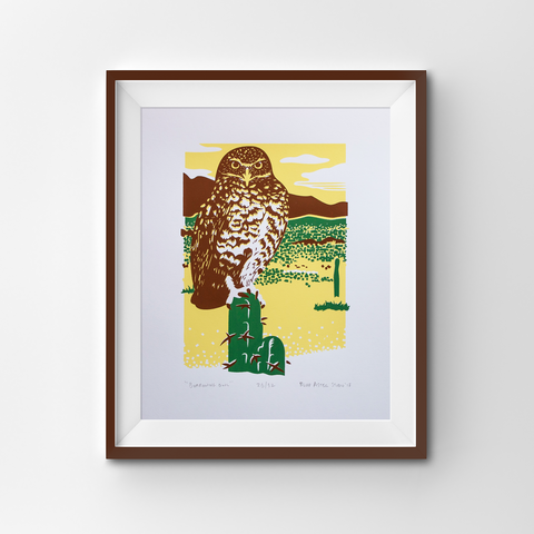 A framed screen print of a Burrowing owl in a desert setting