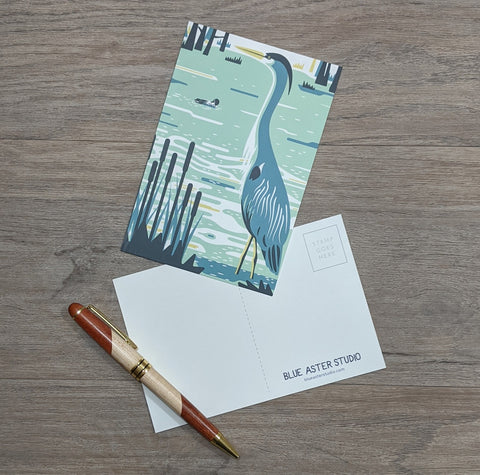 A postcard with an illustration of a great blue heron on it sitting next to a pen.