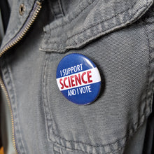 Load image into Gallery viewer, The I Support Science And I Vote button pinned to a gray canvas jacket.