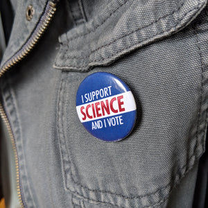 The I Support Science And I Vote button pinned to a gray canvas jacket.