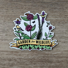 "Load image into Gallery viewer, A vinyl sticker with illustrations of native midwestern US plants such as wild ginger, common milkweed, liatris, bee balm, and echinacea with critters all around them including birds, butterflies, and other insects. At the bottome of the sticker there is a banner that reads ""Garden For Wildlife"""