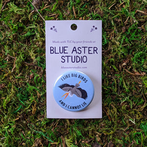 "A 1.5"" pinback button with an illustration of a great blue heron on a light blue background and the words ""I Like Big Birds And I Cannot Lie"""