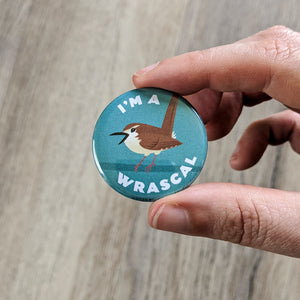 Hand holding the Wren I'm A Wrascal button to show close-up of the wren illustration.