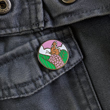 Load image into Gallery viewer, A round monarch butterfly enamel pin on a gray canvas jacket.