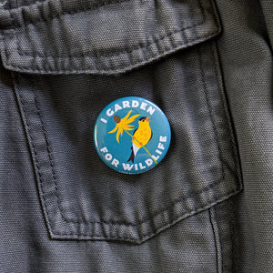 "A 1.5 inch ""I Garden For Wildlife"" button pinned to a gray canvas jacket."