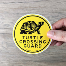 "Load image into Gallery viewer, Hand holding a 3 inch round, yellow vinyl sticker with an illustration of a box turtle and the words ""Turtle Crossing Guard"" in black."