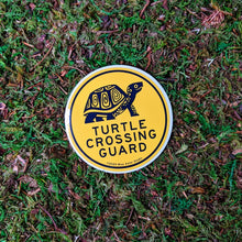 "Load image into Gallery viewer, A round 3 inch vinyl sticker with an illustration of a box turtle and the words ""Turtle Crossing Guard"" in black on yellow. The sticker is sitting on a mossy background."