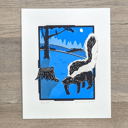 An 8 by 10 inch screen print of a skunk walking in a field in the moonlight past a tree and a stump. It is printed in two shades of blue, gray, and black.