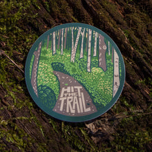 Load image into Gallery viewer, The hit the trail sticker out in the wild with a mossy background.