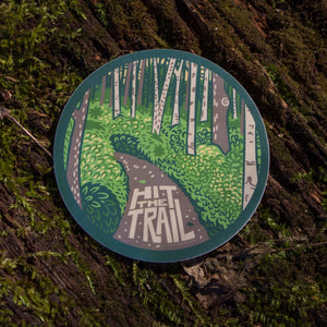 The hit the trail sticker out in the wild with a mossy background.