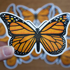 A hand holding a vinyl sticker of a monarch butterfly.