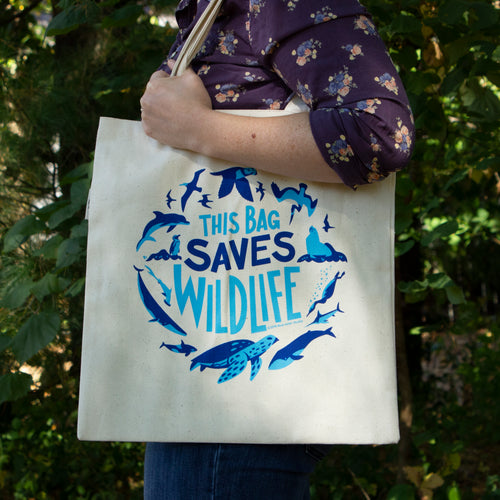 A woman holds an organic cotton tote bag on her shoulder. The bag has the words This Bag Saves Wildlife surrounded by illustrations of sea turtles, sea birds, whales, seals, and other sea life.