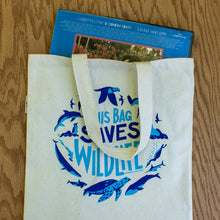 Load image into Gallery viewer, The This Bag Saves Wildlife tote bag holding a record.