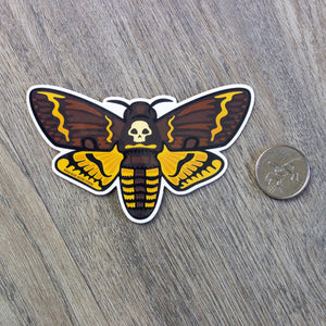 A vinyl sticker of an illustrated deaths head hawk moth next to a USD quarter for scale