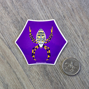 A vinyl sticker of an illustration of an orb weaver spider in a hexagon purple shape