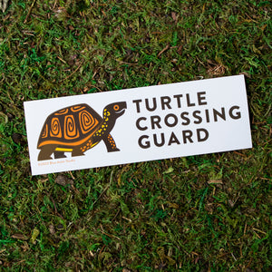"A 2.5 by 7.5 inch vinyl bumper sticker with an illustration of a box turtle and the words ""Turtle Crossing Guard"" next to the illustration."