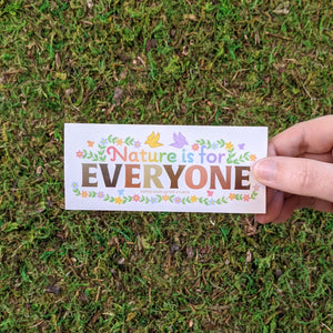 "Hand holding a rectangular vinyl sticker with the message ""Nature Is For Everyone"""
