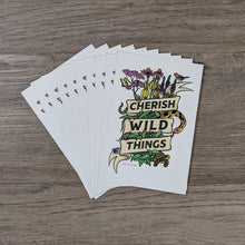"Load image into Gallery viewer, A stack of 10 postcards with a message of ""Cherish Wild Things"" and illustrations of prairie plants and critters."