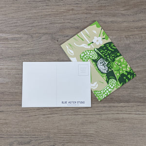 A stack of eastern box turtle postcards with one flipped over to show the detail of the back of the card featuring the Blue Aster Studio logo.