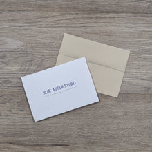 Load image into Gallery viewer, The back of the opossum card showing the Blue Aster Studio logo, website address, and that the cards are printed on recycled paper. The card is sitting next to the natural brown envelope.