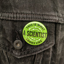 Load image into Gallery viewer, The green This Is What A Scientist Looks Like button pinned on a black jean jacket.