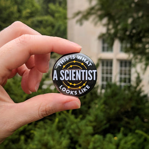 The black This Is What A Scientist Looks Like button being held up in front of limestone campus buildings and greenery.