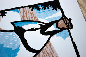 A close-up of the screen print just showing the blue jay's head and beak holding the acorn.