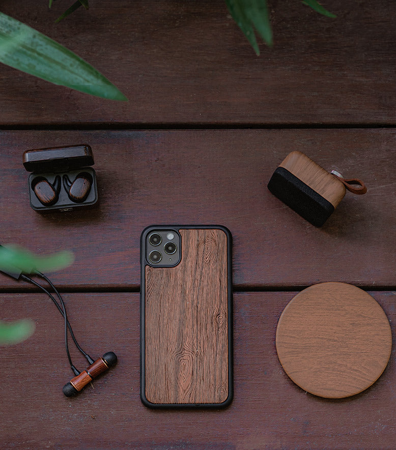 Eco-friendly audio and tech accessories sitting outside on wood in natural surroundings.