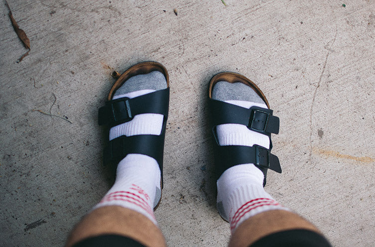 A person looking down at their feet while wearing Birkenstock sandals.