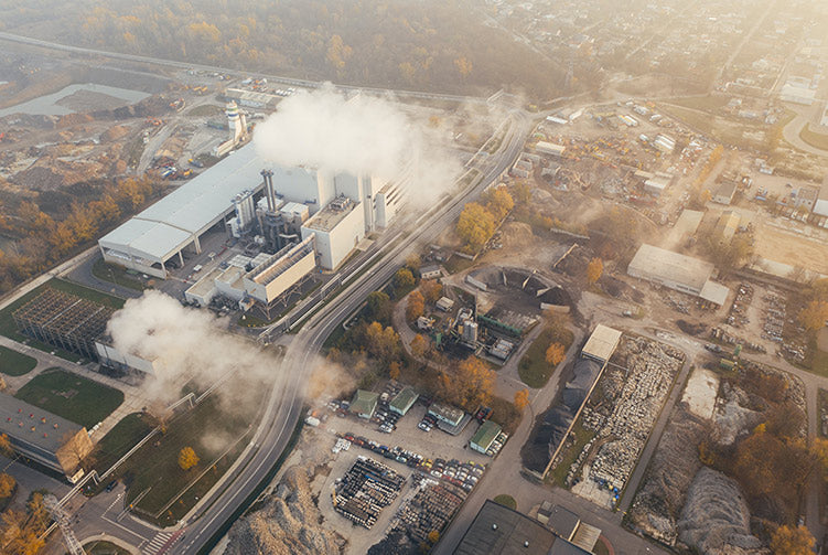 An aerial image of a factory producing large amounts of smog and pollution.