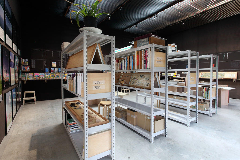 Four industrial bookshelves form the core of the archive. Rather than live behind the scenes, they are the dominant visual element in the gallery space. Photo courtesy of Motoyuki Shitamichi.
