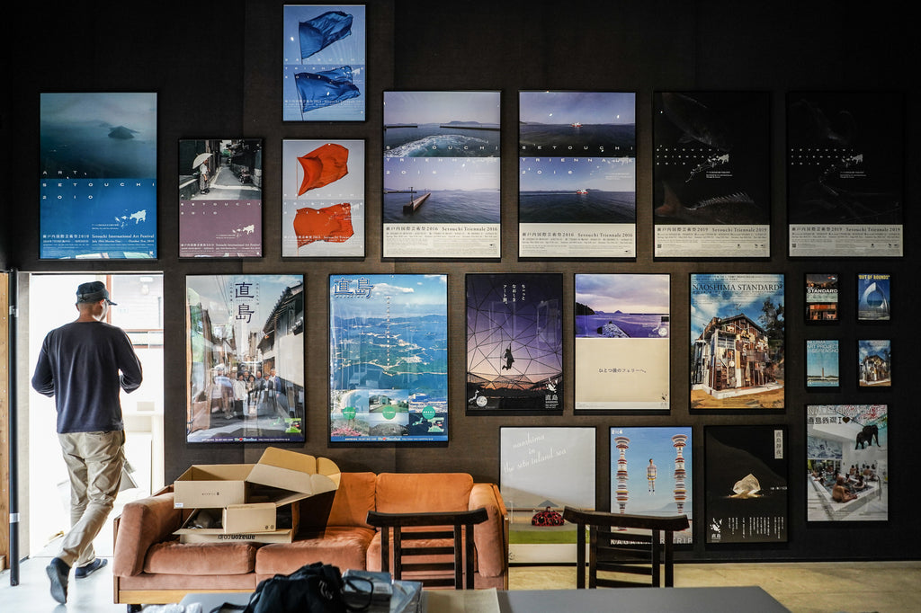 A wall of posters promoting tourism to Naoshima, including several from the Setouchi Triennale. At the time of the interview, the space was being transformed back into a gallery from a temporary theater where Shitamichi showed films set in the region.