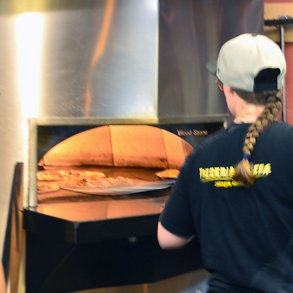 Katie Denton working the pizza oven at pizzeria caldera