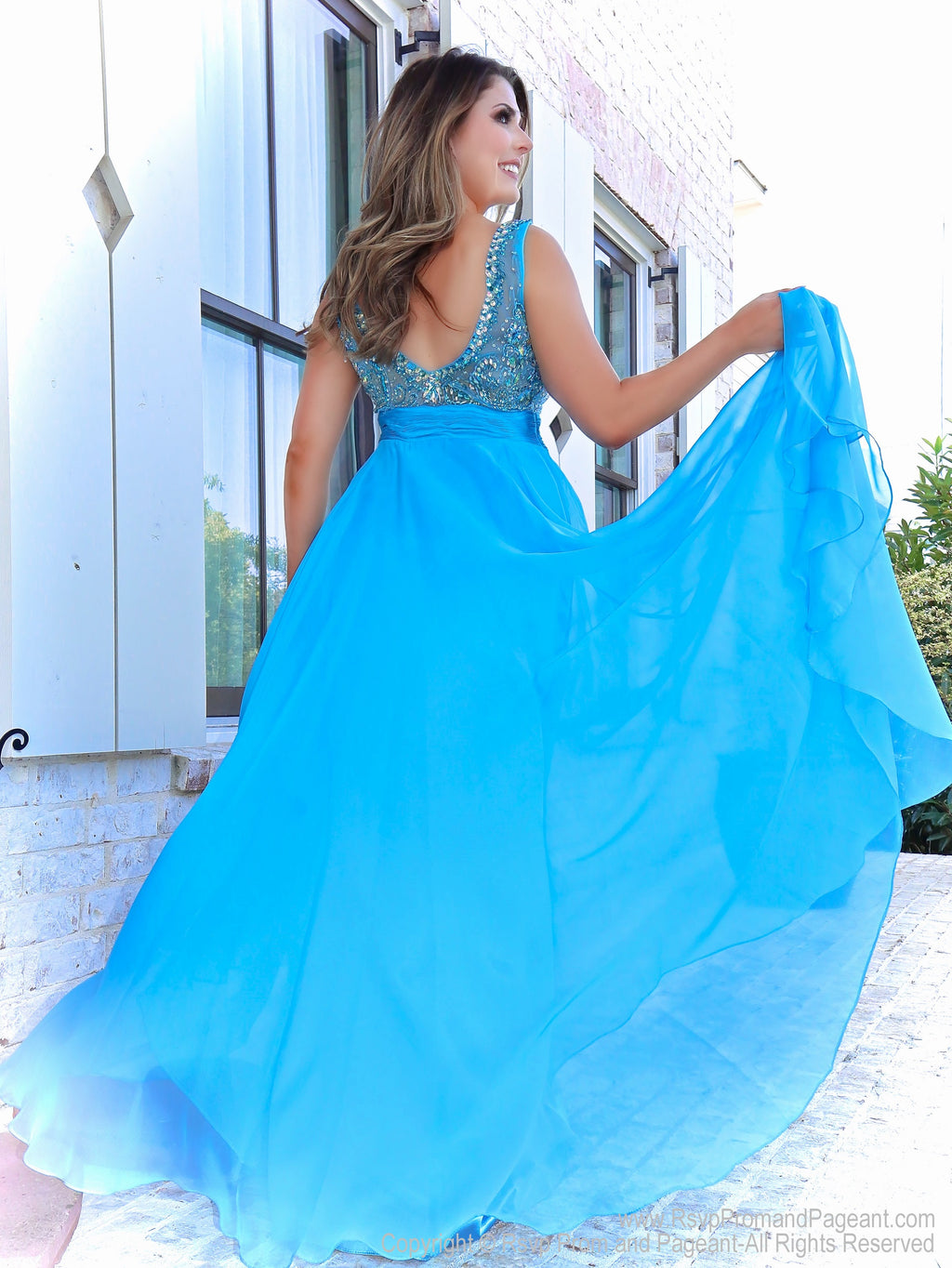 Back of Brunette in a sweet A-line gown has a beautifully beaded neckline and a rouched waistline over the full flowing chiffon skirt. And it's at Rsvp Prom and Pageant, your source of the HOTTEST Prom and Pageant Dresses and Exclusive Evening Gowns and located in Atlanta, Georgia!