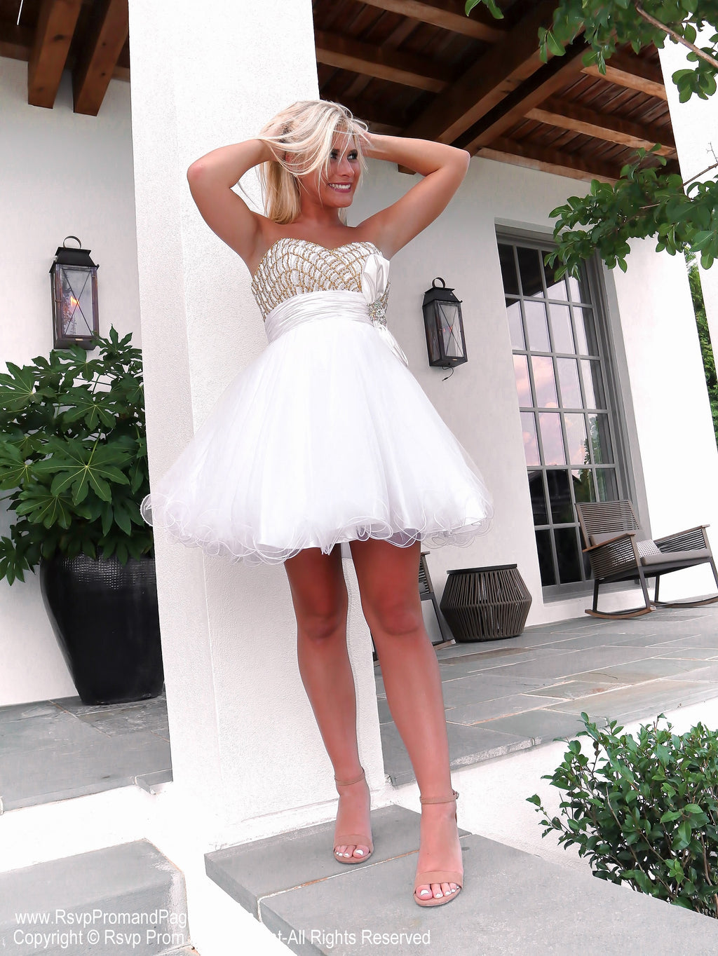 Model holding hair in Darling White Short Homecoming Dress with Gold Bodice and Bow at Rsvp Prom and Pageant, the best prom dress store in Atlanta, Georgia