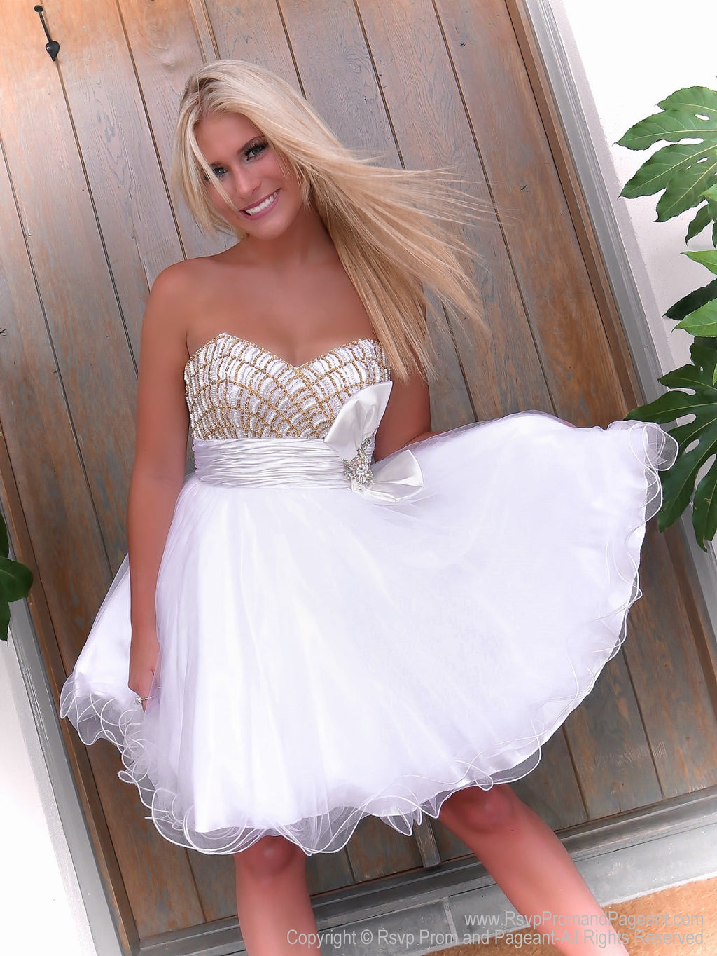 Pretty blonde model in Darling White Short Homecoming Dress with Gold Bodice and Bow at Rsvp Prom and Pageant, the best prom dress store in Atlanta, Georgia