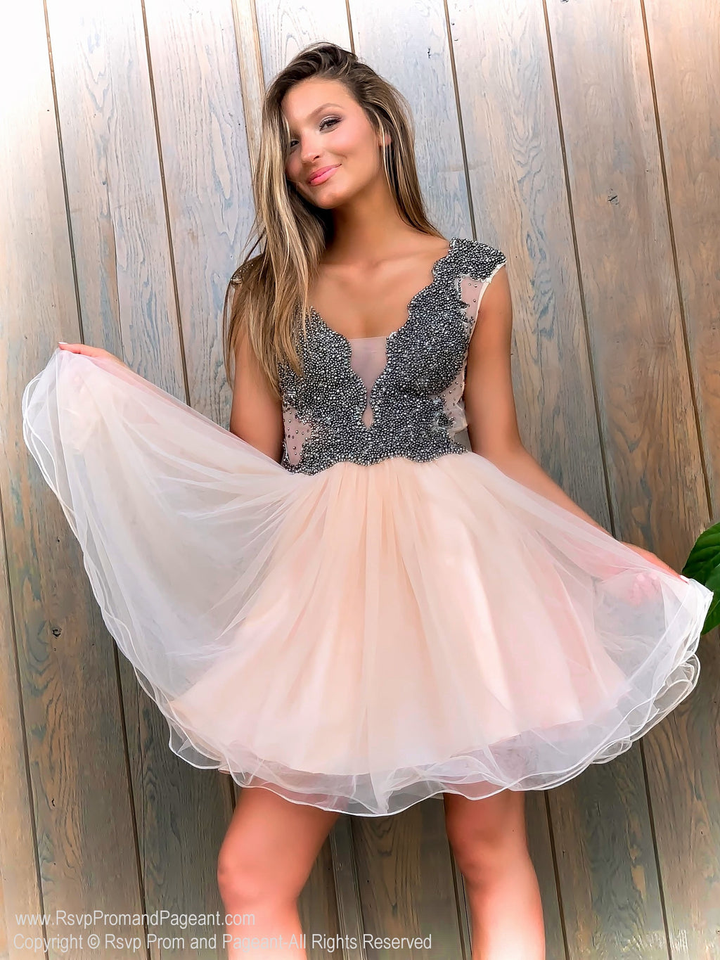 Brunette posing in a Fabulous Short Dress with Completely beaded Top and Full Tulle Skirt at Rsvp Prom and Pageant, the largest prom dress store in the Southeast USA located in metro Atlanta, Georgia