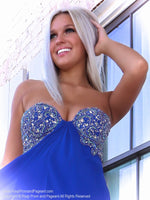 Closeup of Model in a royal blue prom dress that's so pretty with a classic empire waist and beadwork in various hues of blue, and a delicate chiffon skirt. And it's at Rsvp Prom and Pageant, your source for the HOTTEST Prom and Pageant Dresses and Exclusive Evening Gowns and located in Atlanta, Georgia!