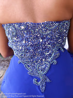 Closeup of back of Model in a royal blue prom dress that's so pretty with a classic empire waist and beadwork in various hues of blue, and a delicate chiffon skirt. And it's at Rsvp Prom and Pageant, your source for the HOTTEST Prom and Pageant Dresses and Exclusive Evening Gowns and located in Atlanta, Georgia!