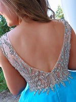 Closeup of back of model feeling like a true princess in this beautiful blue evening gown! The bodice is adorned with the most exquisite stone work leading to a light and flowing chiffon skirt. And it's at Rsvp Prom and Pageant, your source for the HOTTEST Prom and Pageant Dresses and exclusive evening gowns and located in Atlanta, Georgia!