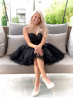 Blonde model sitting on swing in Adorable Black Lace Short Homecoming Dress at Rsvp Prom and Pageant, best prom dress store, Atlanta, Georgia