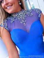 Closeup of an elegant royal blue formfitting dress. The high illusion sweetheart neckline features sparkling crystal beadwork cascading over the cap sleeves and an open back to complete this fabulous look! And it's at Rsvp Prom and Pageant, your source for the HOTTEST cocktail, homecoming, prom and pageant dresses located in metro Atlanta, Georgia!